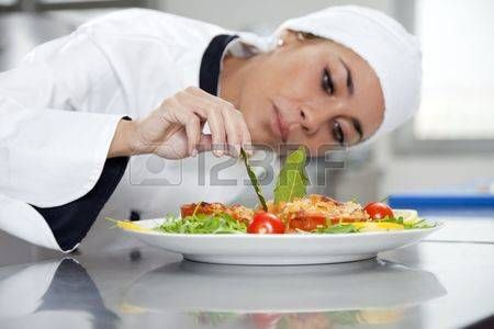 female chef: mid adult female chef in kitchen decorating dish