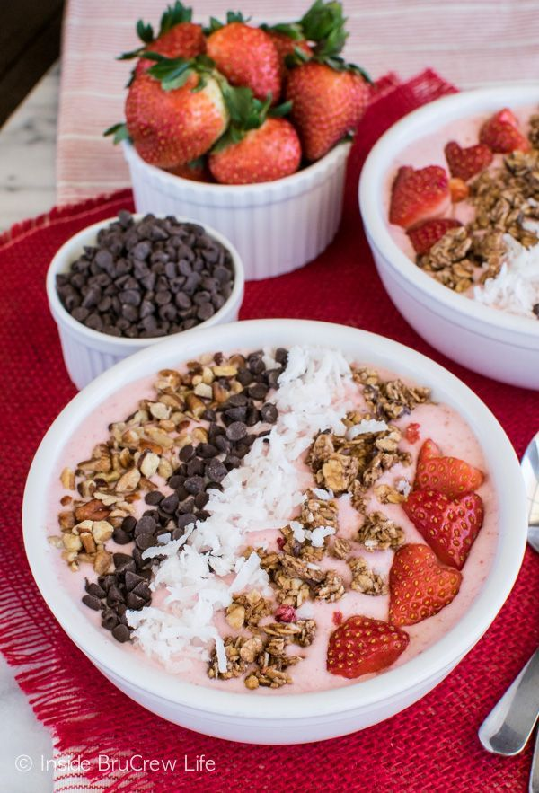 Strawberry Coconut Smoothie Bowl recipe - strawberry smoothie topped with nuts, chocolate, berries, & coconut. It's a delicious breakfast or snack option.