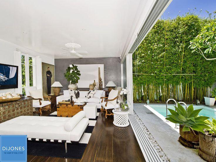 White walls, wood floor, plants, pool, bamboo, tree trunk pots