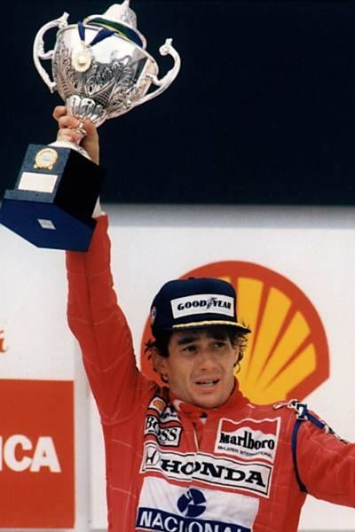 Ayrton Senna struggles to lift the trophy having pushed his body to the edge in the quest to win his home Grand Prix in São Paulo 1991.