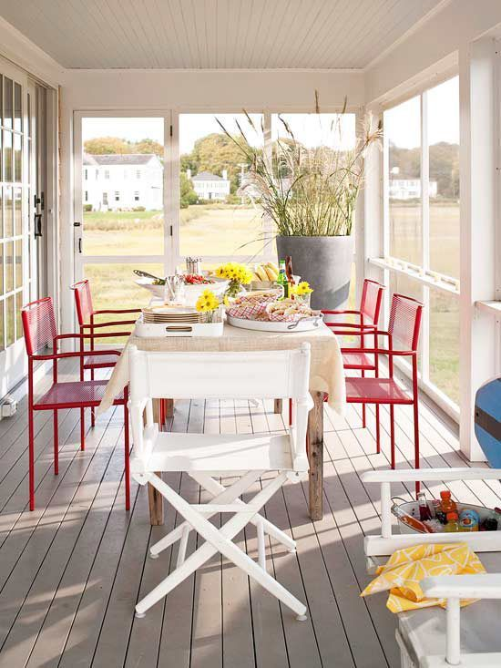 A narrow screened porch off the back of this home provides a summery dining spot for the whole family. The red-painted chairs along the sides of the dining table add a splash of color to the neutral space. Screens on all of the windows act as barriers that help keep out unwanted critters and crawlers./