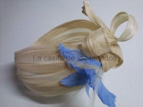 turbante para boda, realizado con sinamay de seda en color beige y adorno de plumas en color lila