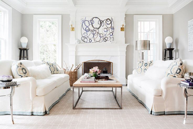 Chic, elegant living room boasts white skirted sofa with blue trim adorned with geometric pillows