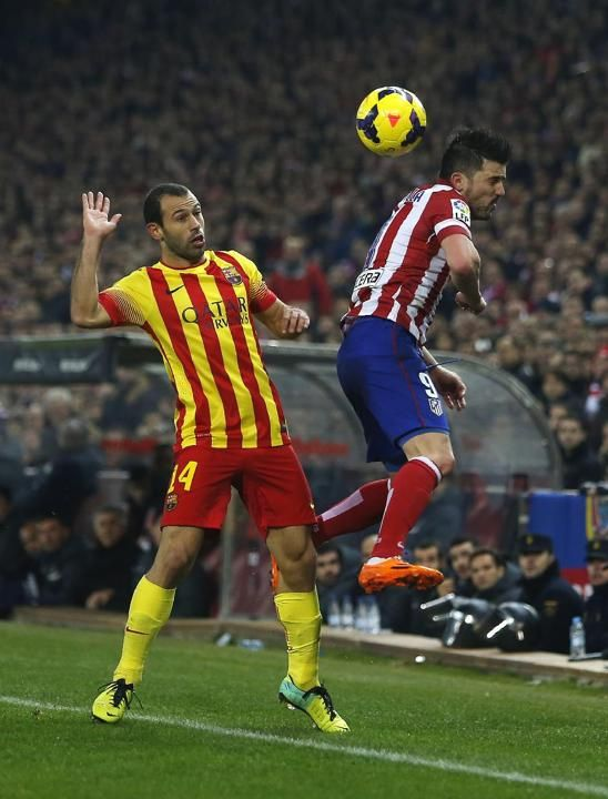 Barcelona's Javier Mascherano from Argentina, left, in action with Atletico's David Villa, right, during a Spanish La Liga soccer ma...