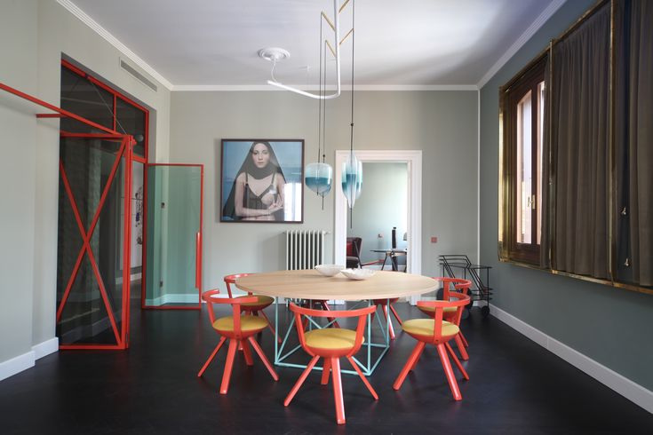 a LC15 table by Le Corbusier for Cassina, Rival Chairs by Konstantin Grcic for Artek with Kvadrat fabric, a bar cart by Rossana Orlandi, and Flow pendant lights by Wonder Glass.