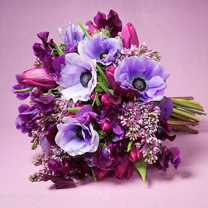A purple anemone, lilac, sweet pea, and tulip bouquet.  Browse more bouquets for a modern wedding.