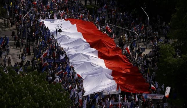 Tens of thousands of Poles waving national flags staged a huge protest march through Warsaw on Saturday, accusing the conservative Law and Justice (PiS) party that took power last year of undermining democracy and putting Poland's European future at risk.