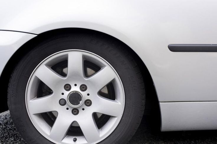 Car wheel on a modern white vehicle viewed from the side showing the spokes of the hub and rim in a close up cropped view with copy space - free stock photo from www.freeimages.co.uk