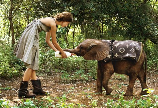 "All Creatures Great and Small Knightley feeds an orphaned elephant at the David Sheldrick Wildlife Trust. ""There were three of them, and they were all so cheeky, rolling around in the dust and trying to knock us all over.\"" Bottega Veneta dress. Frye boots."
