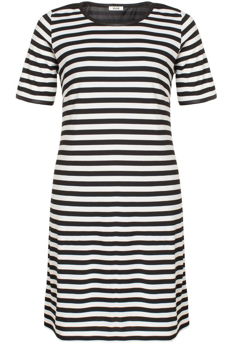 Gestreepte jurk met een onderjurk van het merk Anna in de kleuren zwart en wit. De jurk is iets uitlopend en heeft korte mouwen. Bij de hals en schouders zit een zwart imitatieleren biesje.