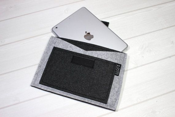 Modern and simple felt iPad / tablet sleeve case of Melange black and light grey color. V line pocket makes it easy to take items out. Water repellent finishing for very light watery condition. Pockets for personal items on the front. Your tablet would be safe from dust, scratches and minor damage.  • Made to order. Production time 3~5 days after payment cleared. • Materials: Made with felt material with velcro tape for closure. • Care: Spot clean • This sleeve fits iPad pro / iPad air…