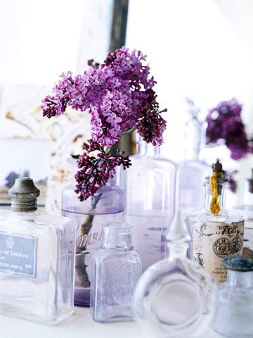 Multiple vases made from perfume bottles, lotion and ball jars.  Nice setting for a sea shore home!