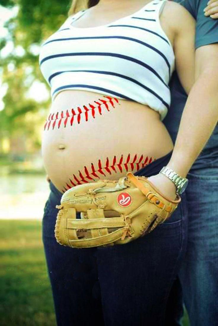 Sesión de fotos de maternidad chica con su vientre pintado como una pelota de beisbol