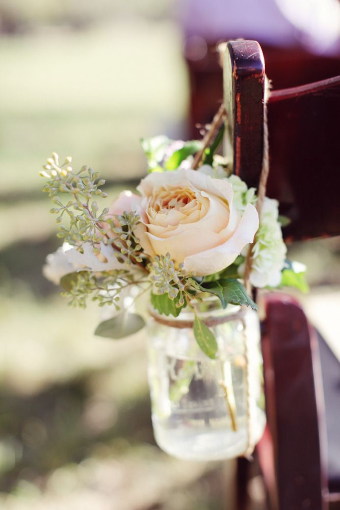 Hanging mason jars with floral arrangements of blush on aisle chairs at ceremony