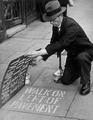 World War 2: 'Walk on the left' signs are painted on the pavement at 400 points in Southgate in order to cut down pavement collisions in the black-out. October 14, 1942.