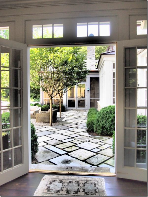 outdoor patio pavers with grass/thyme in between....trees planted within patio, large windows/doors with glass