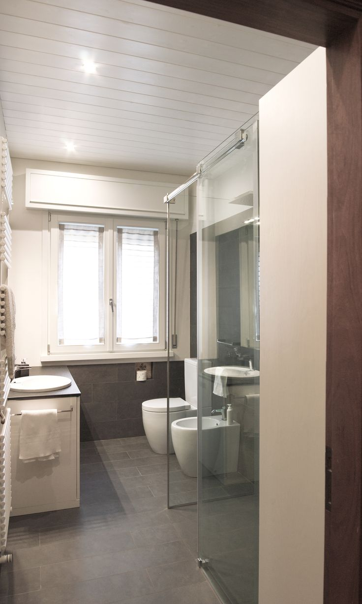 renewed bathroom in apartment from the '70: grey tiles, whitened wood and glass