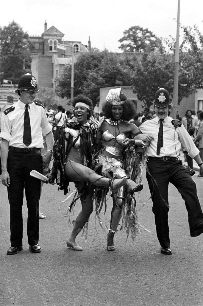 Police constable John Corbett joins an impromptu knees-up with Notting Hill Carnival revellers. PC Corbett, from Harrow Road police station, found his can-can partners on the second day of the August Bank holiday festival. Ref #: PA.7740097  Date: 30/08/1982