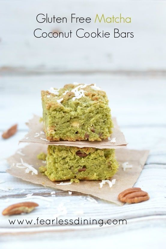 Gluten Free Matcha Green Tea Coconut Cookie Bars stacked on paper with pecans around it.
