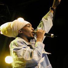 Anthony B - Drappeggiato nei ricchi colori dell'abbigliamento africano, il suo marchio di fabbrica in mano e la sua capigliatura rasta regalmente avvolta intorno alla testa, Anthony B incarna tutto ciò di più spirituale e positivo che c'è nella musica reggae. Questo a...