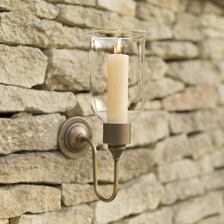 A charming, #antiqued #brass #candle wall sconce with a clear glass shade, making it ideal for #outdoor situations as the wind won't blow out your candle so easily