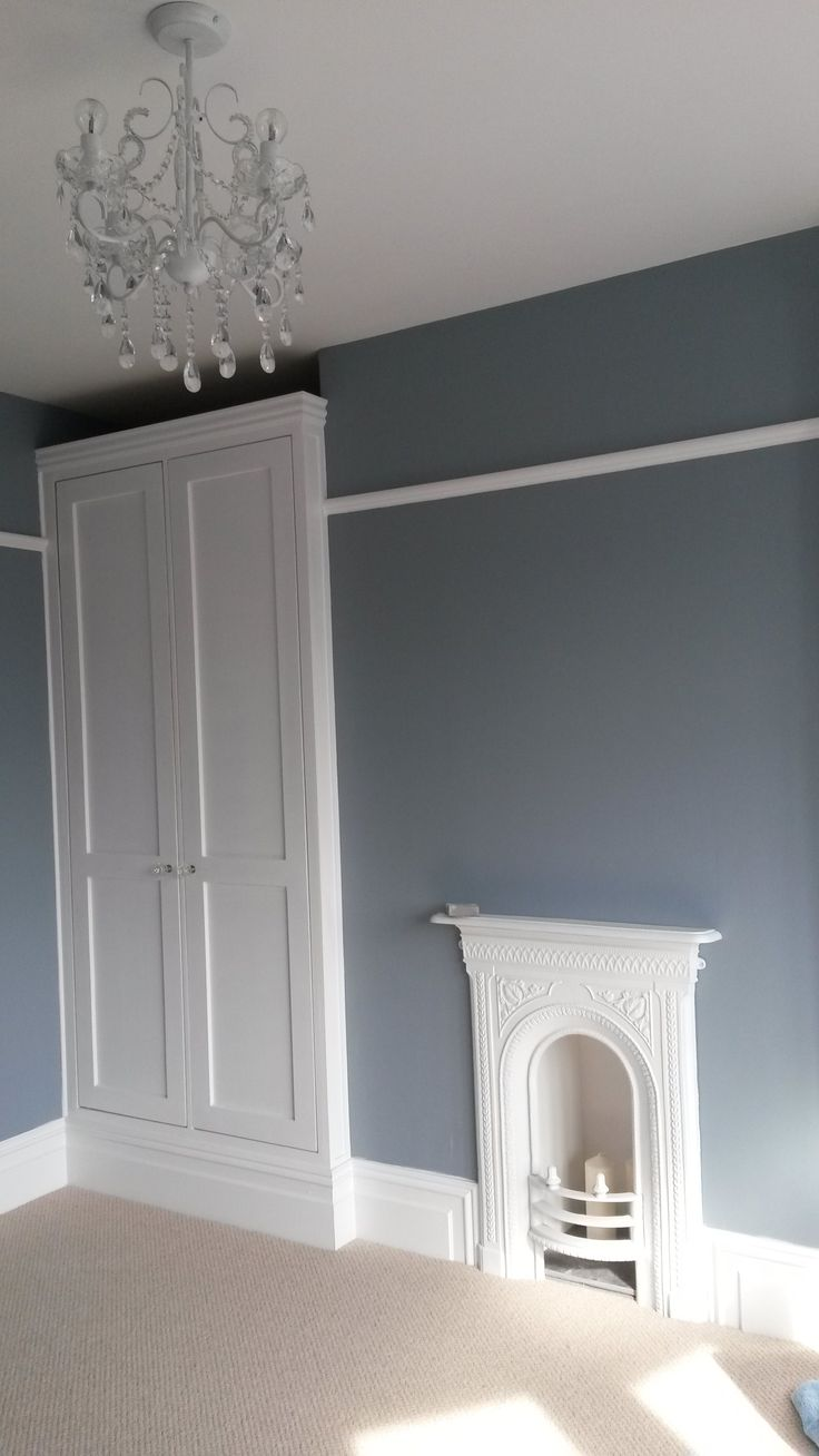 Bespoke fitted wardrobes and cast iron fire place in bedroom 1. Walls painted in steel symphony 3