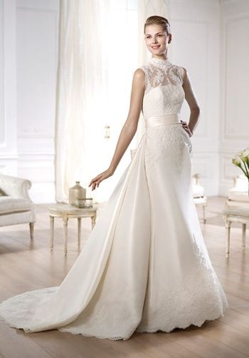 Pronovias Costura Collection -- Ondra  Grace Mikado dress with detachable train. Rebrodé lace bodice with turtleneck and sheer off-the-shoulder overbodice. Pleated sash at the waist that hides the start of the train. A-line silhouette skirt with rebrodé lace appliqués at the waist and hem.