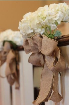 Burlap bows and flower bunches decorated the church pews