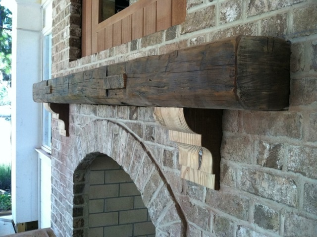 stone fireplace with reclaimed wood mantel and corbels