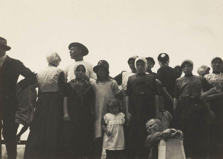 Een groep mannen, vrouwen, meisjes en jongens van het eiland Urk. De meesten zijn gekleed in streekdracht en enkelen dragen modekleding. 1927 #Urk