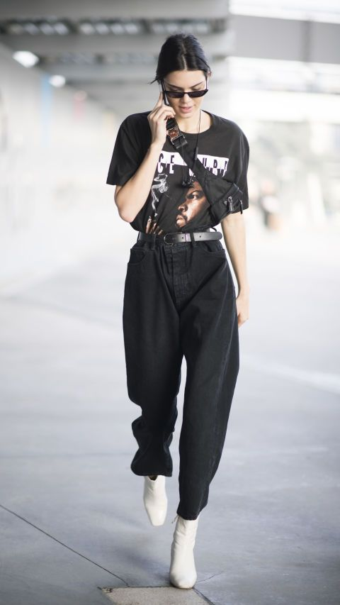 Kendall Jenner sporting a vintage Ice Cube t-shirt, baggy black jeans cinched in at the waist and white ankle boots is a simple and comfortable stylish look we can't resist.
