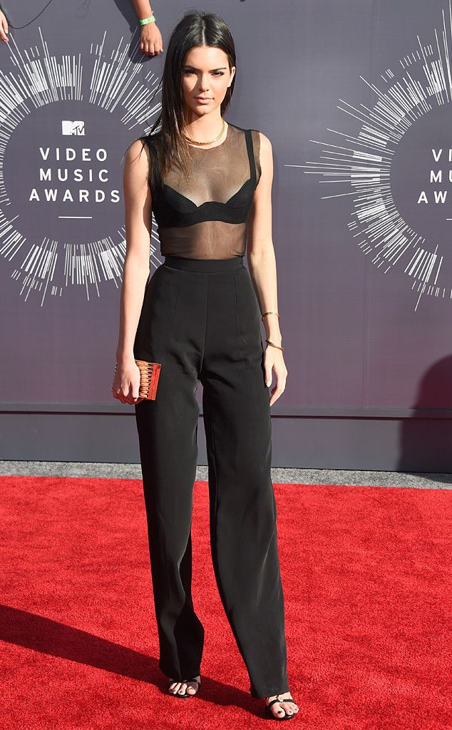 Kendall Jenner looks runway-worthy in a black mesh top, matching pants and simple strappy sandals.