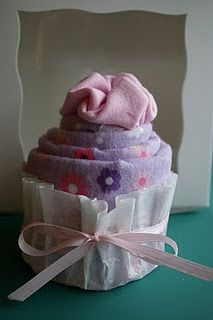 im obsessed with these, another alternative for diaper cakes, and so much cheaper, they have put theirs in a box but i think it would look cool on a cupcake stand, or a diy stand from plates and candle holders!