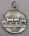 """A well modelled silver equestrian medal, showing a horse rider with hounds on the front, and 3 horses in a field with a tree on the rear. It reads """"Hunters Improvement and National, Light Horse Breeding Society, 1932"""". The medallion was modelled by Frank Hyams Ld, as indicated by his signature.   Leopard Antiques Small Collectables"""