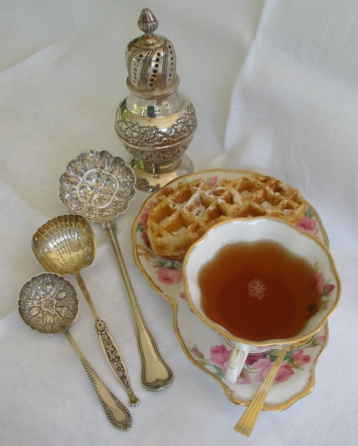 Tea French Style: Pierced French Christofle Sugar Sifter Spoon from 1862 in the Filet Violon pattern. It is used for dusting powdered sugar on crepes or waffles. Center is an antique French spoon that is gilded.  In the back is a silver muffineer.