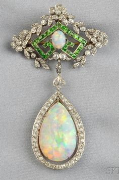 Edwardian Opal, Demantoid Garnet, and Diamond Pendant/Brooch, set with a large cabochon opal drop within an old mine-cut diamond frame, suspended from an old mine-cut garland with calibré-cut demantoid garnets, platinum-topped 14kt gold mount.