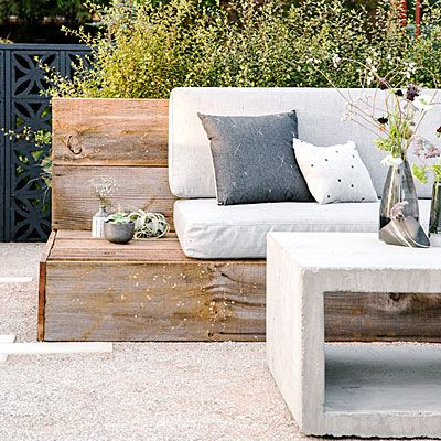 Entertain away - An oversize L-shape bench made from recycled wood creates a perfect seating area for hosting or lounging.  Slate-grey cushions and graphic pillows coordinate with the hand-poured concrete table.