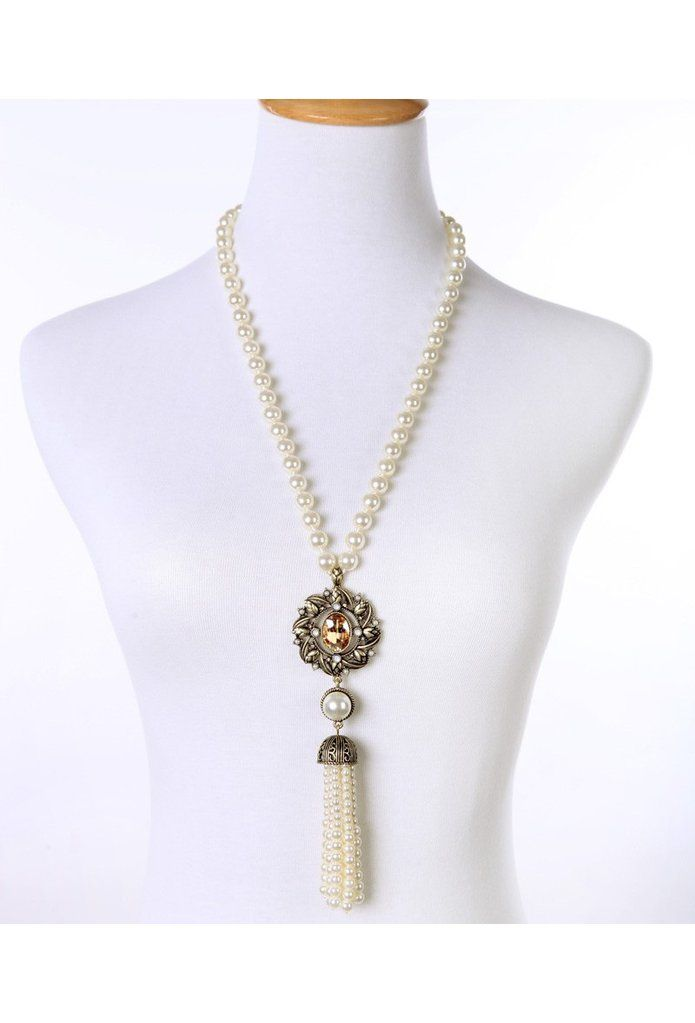 A beautiful addition to your Gatsby look, this necklace features iconic pearls with an amber Marquise gold-tone pendant. A gorgeous beaded tassel completes the