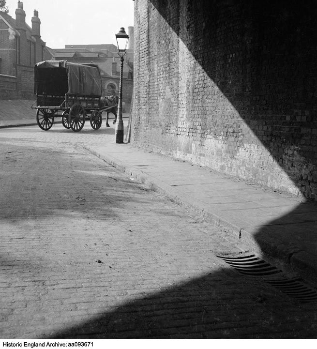 AA093671 A covered horse-drawn cart belonging to the LMS railway company passes a gas lamp on a street corner.  Place:Greater London    Date1945 - 1950 Photographer: John Gay