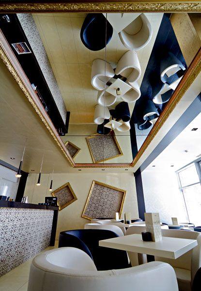 Oblé čalúnené kreslá z čiernej a bielej kože dopĺňajú štvorcové stolíky #ASB #interior #design #café