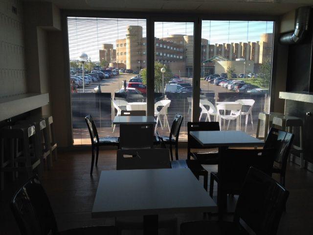 Al fondo Hospital y la terraza con sillas de PVC blanco
