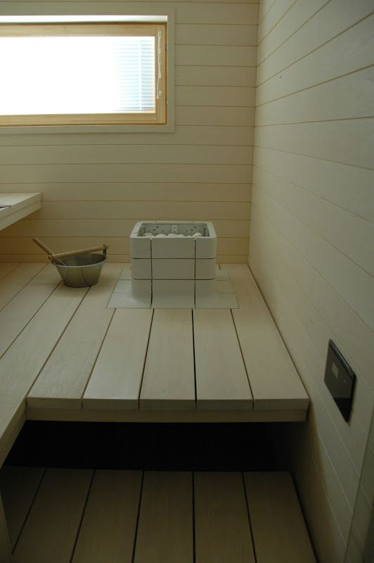 Tulikivi Nuoska heater and control unit on the wall in this beautiful light sauna. moderni puutalo: Sauna pähkinänkuoressa