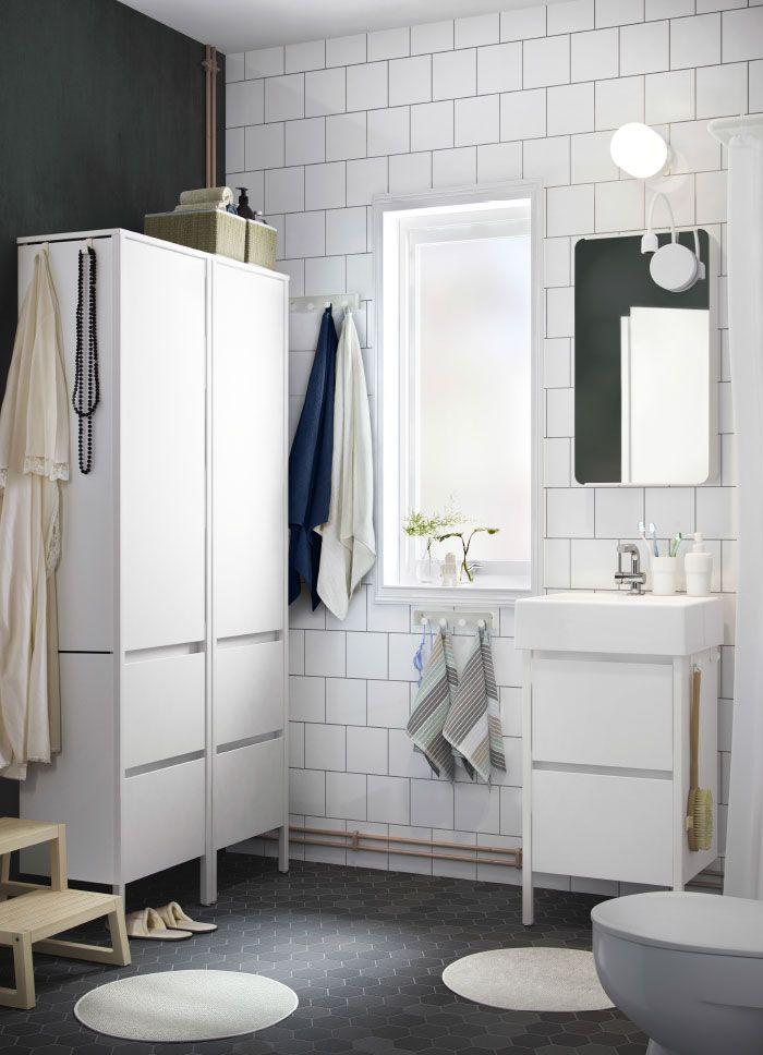 Lite, hvitt bad med to hvite høyskap, et speil og et servantskap med to skuffer.