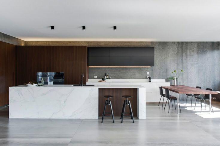 Carrelage béton ciré grand format et îlot en marbre blanc dans une cuisine minimaliste