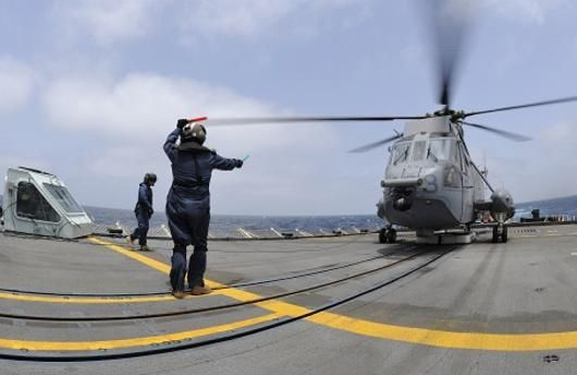 A flight deck crewmember on Her Majesty's Canadian Ship Toronto guides in a Sea King.