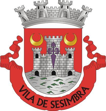 """Brasão de Sesimbra - Official blazon  Escudo de vermelho, com um castelo de prata de três torres, sendo a do meio carregada de uma cruz da Ordem de Santiago e as dos flancos por um crescente de ouro; o castelo banhado por um mar de prata, aguado de verde. Coroa mural de prata de três torres. Listel vermelho com a legenda a negro, em maiúsculas: """" SESIMBRA """".Freguesias in Sesimbra :      Castelo (Sesimbra)     Quinta do Conde     Santiago (Sesimbra)"""