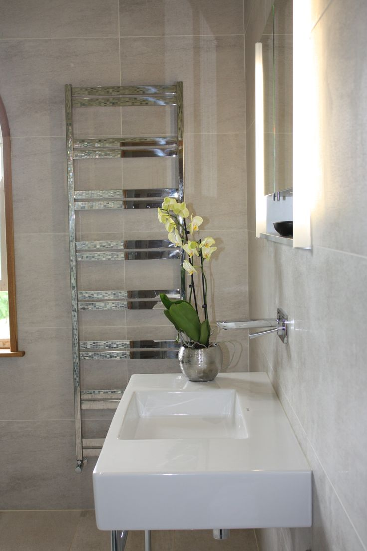 Polished radiator reflects the mosaics in the shower. Copyright The Designer Knowledge.