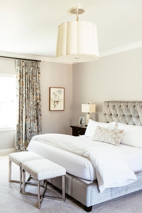 Gray bedroom features walls painted warm gray lined with a gray velvet tufted bed dressed in crisp white bedding next to a dark stained nightstand and alabaster lamp, Oval Stacked Table Lamps.