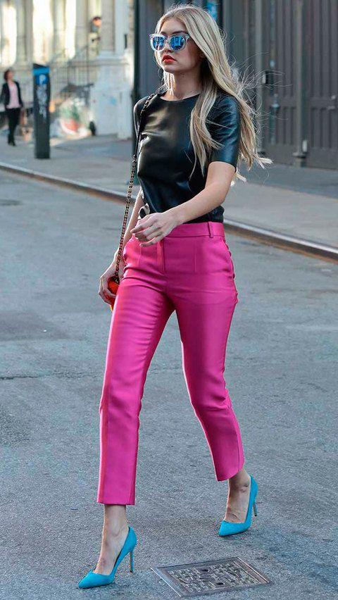 Con pantalones con brillo fucsia, camiseta negra de cuero, salones color turquesa y gafas de espejo con montura transparente.