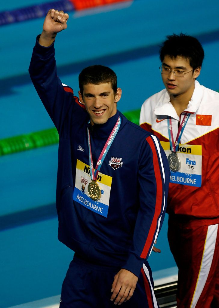 Michael Phelps Photos Photos - Michael Phelps of the USA (L) poses with his gold medal following his win and new world record in the Men's 200m Butterfly Final during the XII FINA World Championships at the Rod Laver Arena on March 28, 2007 in Melbourne, Australia. - XII FINA World Championships - Day 12